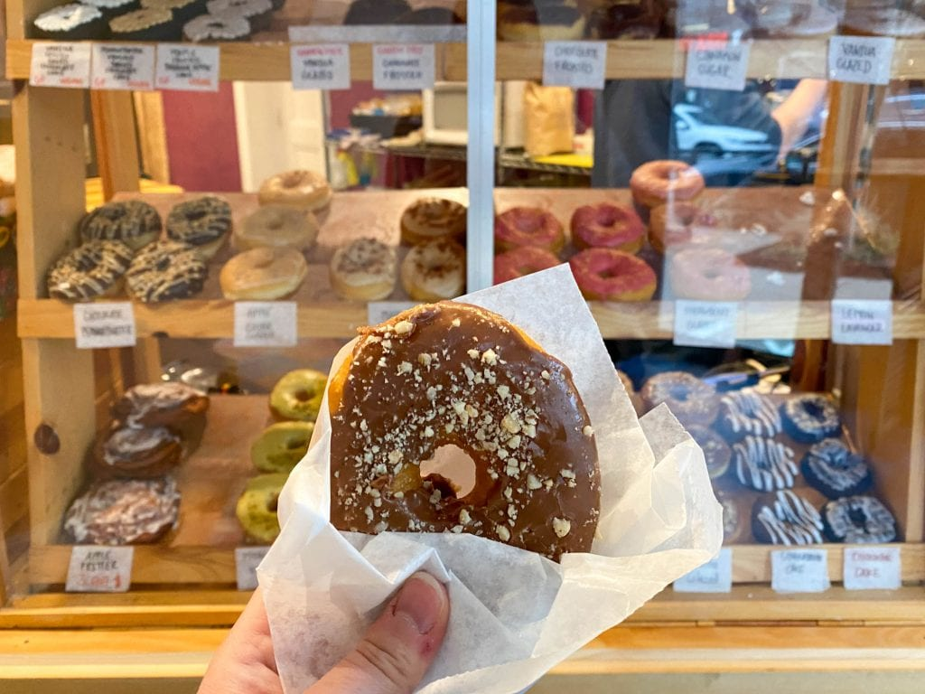 Bigmouth donut held up in front of donut case.